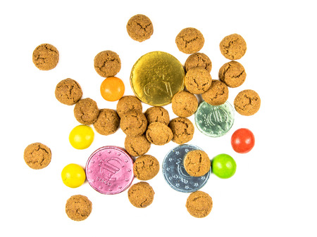 Bunch of scattered pepernoten cookies, chocolate money and sweets from above on white background for annual Sinterklaas holiday event in the Netherlands on december 5th