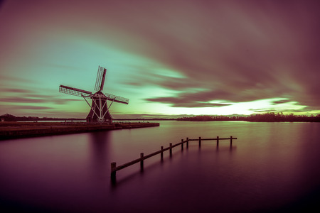 Tradional wooden windmill on the waterfront of a lake under long exposure sunset in the Netherlands in vintage toning Stockfoto