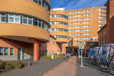 GRONINGEN, NETHERLANDS - FEBRUARY 2, 2017: Entrance of Universitair Medisch Centrum Groningen or UMCG academic Hospital with bicycle parking and cycling lane