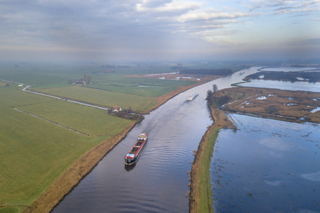Aerial view of canal in Friesland with inland freight ships passing by. The Netherlands Stockfoto