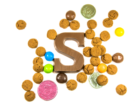 Bunch of Pepernoten strooigoed with chocolate letter S, top view on white background for annual Sinterklaas holiday event in the Netherlands on december 5th