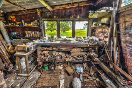 Extremely messy workbench in a wooden barn as sign of compulsive hoarding