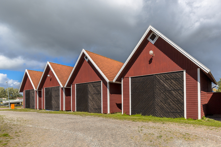 Swedish wooden storehouses in red color under clouded summer sky