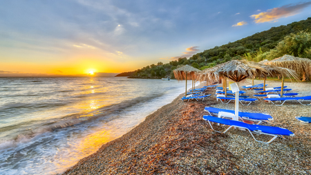 Straw umbrellas with blue beach beds at sunset on Peloponnese beach, Greece Imagens