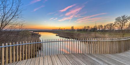 Bright sunset over Wooden deck balcony of bridge in Onlanden Nature reserve waterlogging area Groningen, Netherlands