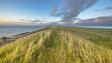 Afsluitdijk dutch dike with fence motorway and cycling track during  sunset with clouded sky Stockfoto - 119682490