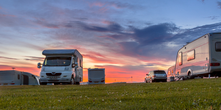 Camping caravans and cars parked on a grassy campground under beautiful sunset Reklamní fotografie
