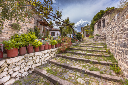 Rocky stairs in alleyway with green plants in the historic village of Molyvos, Lesbos, Greece