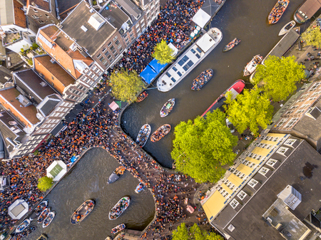 Canal boat parade on Koningsdag Kings day festivities in Amsterdam. Birthday of the king. Seen from helicopter. Stock Photo