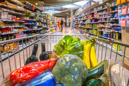 Boodschappenwagentje in supermarkt gevuld met voedingsproducten gezien vanuit het oogpunt van de klant