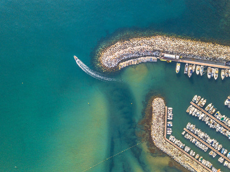 Marina top down aerial view with boat sailng off in mediterranean Sea in Saint Aygulf near Frejus Cote dAzur, France