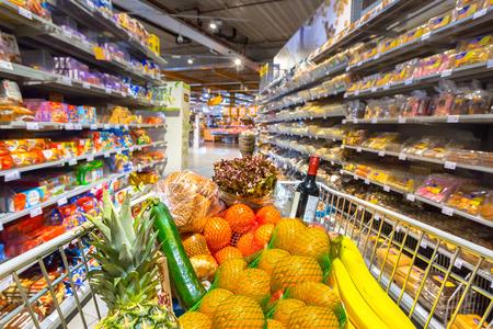 Wózek spożywczy w supermarkecie wypełniony produktami spożywczymi widziany z punktu widzenia klientów