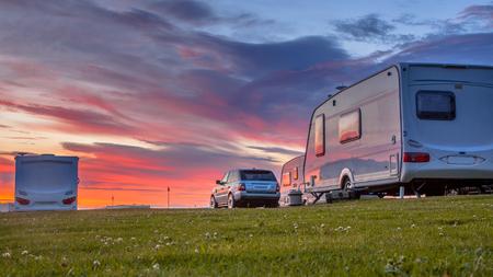 Caravanes de camping et voitures garées sur un terrain de camping herbeux sous un beau coucher de soleil