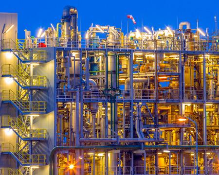 Szczegół pionowego portretu ciężkich zakładów chemicznych o zmierzchu na terenie fabryki przemysłowej