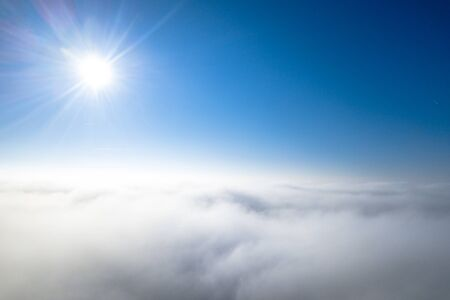 Aerial view of mist layer from above looking like sun shining above clouds