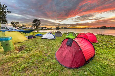 Campingplatz mit Kuppelzelten in der Nähe des Sees auf einem Musikfestivalcampingplatz bei wunderschönem Sonnenaufgang Standard-Bild