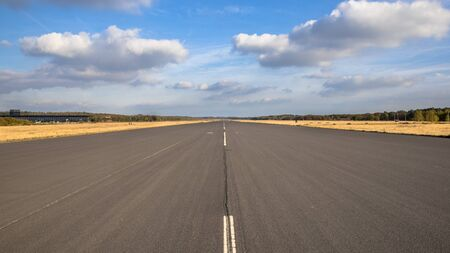 Runway on airport on clouded sunny day with blue sky