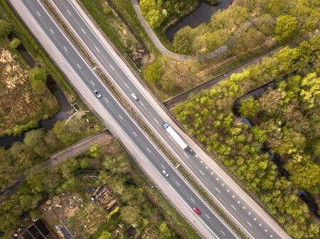 Aerial view of four lane motorway with emergency lane and moderate traffic during rush hour Фото со стока