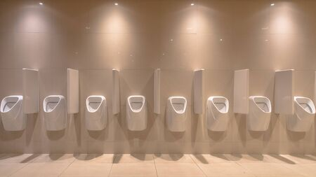 Row of modern Urinals in new bathroom of Theater