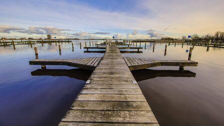 Empty wooden jetty in marina on lake shore in friesland, The Netherlands 版權商用圖片