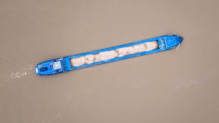Top down view on inland freight ship loaded with sand in dutch river Rhine