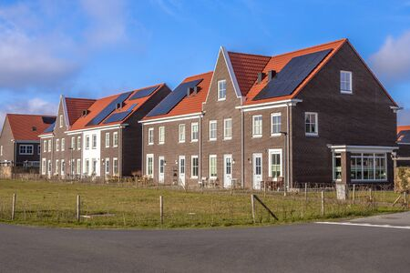 Modern row houses with solar panels, brown bricks and red roof tiles in neoclassical style in Groningen Netherlands under blue sky