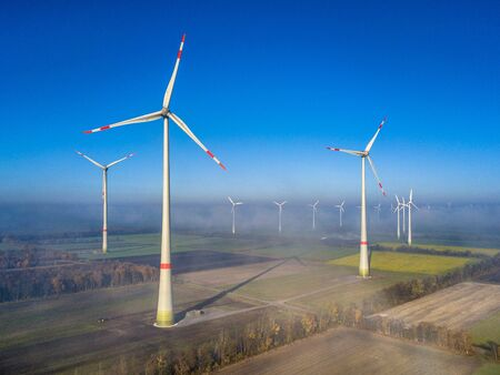 Aerial view of wind energy turbines on windfarm above mist layer on german countryside in the morning sun. Germany Standard-Bild