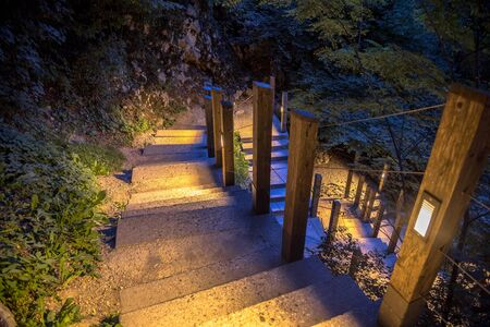 Illuminated outdoor Staircase down rocky mountain park at night