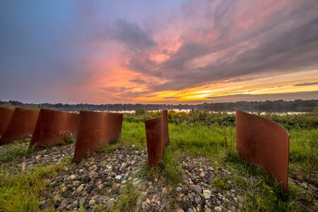 Rusty Metal curved objects in landscape with lake and sunset at Piccardthofplas Groningen city, Netherlands 版權商用圖片