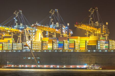 illuminated Cargo carrier ship being loaded and refueled at night in Rotterdam Maasvlakte container terminal in darkness. The Netherlands Stock fotó