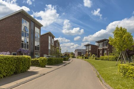 Modern street with large detached family houses in suburb in Groningen Netherlands Stok Fotoğraf