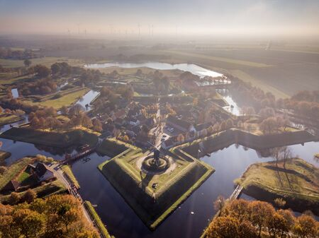 Aerial view of Fortification village of Bourtange. This is a historic star shaped fort in the Province of Groningen seen from above in autumnal colors Standard-Bild - 130816888