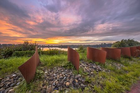 Metal wave objects in landscape with lake and sunset at Piccardthofplas Groningen city, Netherlands