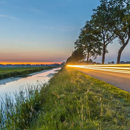 Netherlands open polder landscape with canal and traffic lights on road in open grassland countryside at sunset Reklamní fotografie