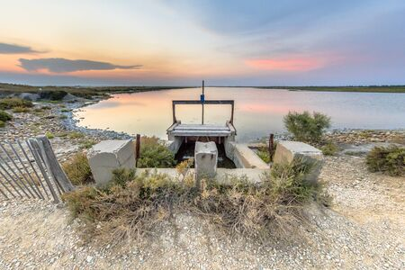 Hydraulic Weir in dam in colorful lagoon under beautiful sunset in Camarque regional nature reserve, Provence Alpes Cote dAzur, France Reklamní fotografie
