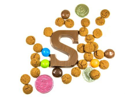 Collection of Pepernoten strooigoed with chocolate letter S, top view on white background for annual Sinterklaas holiday event in the Netherlands on december 5th Standard-Bild