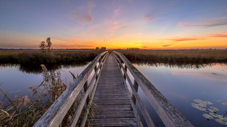 Wooden bridge for bicycles crossing river at sunset, Groningen, Netherlands