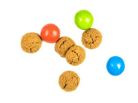 Small Group of scattered pepernoten cookies and sweets from above on white background