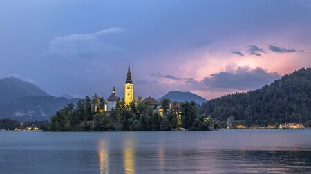 Lake Bled with St Marys church and mountains in backdrop under stormy sky with lightning storm, Slovenia, Europe 写真素材