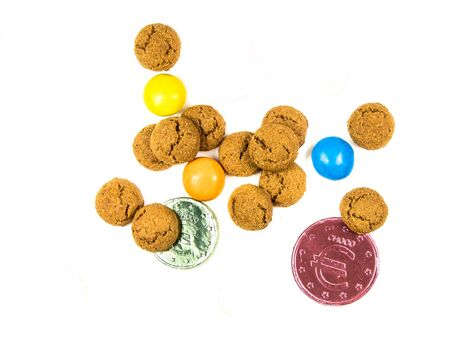 Bunch of pepernoten cookies, sweets and chocolate money from above on white background for annual Sinterklaas holiday event in the Netherlands on december 5th