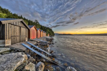 Sunset with Colorful Boathouse in Norwegian fjord near Rodven in More og Romsdal province