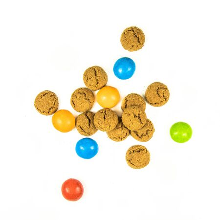 Bunch of scattered pepernoten cookies from above on white background for annual Sinterklaas holiday event in the Netherlands on december 5th