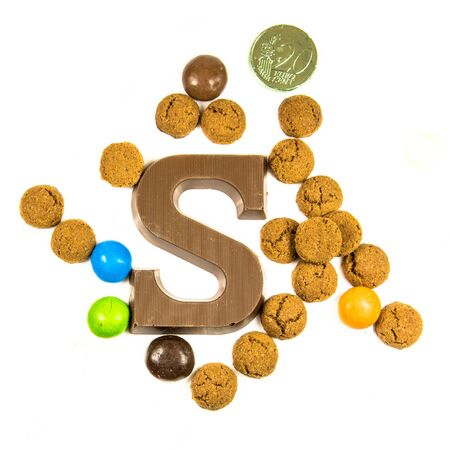 Group of Pepernoten strooigoed with chocolate letter S, top view on white background for annual Sinterklaas holiday event in the Netherlands on december 5th