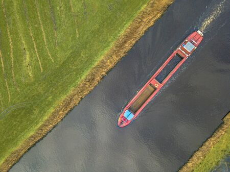 Top down view on inland freight ship in dutch canal