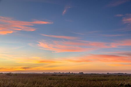 Beautiful sunset background over flat countryside in the Netherlands