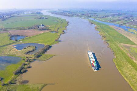 Barge porte-conteneurs sur la rivière Lek vue aérienne près du village de Ravenswaaij, Gueldre, Pays-Bas