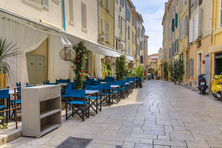 Street with empty restaurant  and terrace in town of Saint Tropez Cote d'Azur, Southern France