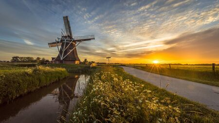 Dutch wooden windmill along cycling track at sunset in summer field with flowers and beautiful sky