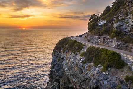 Winding road along rocky coast of Cap Corse peninsula on Corsica island at sunset, France