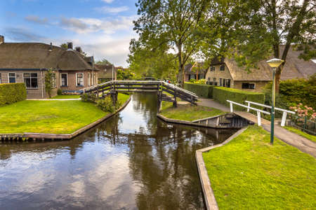 Landscape view of famous Giethoorn village with canals and rustic thatched roof houses in farm area. Overijssel, Netherlands. September